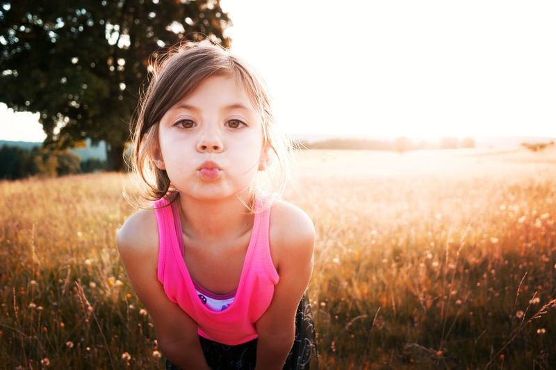 Portrait of girl puckering lips while standing on field during sunny day