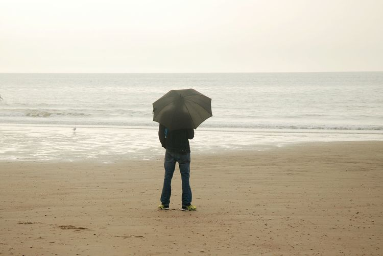 Man with umbrella standing at beach against clear sky