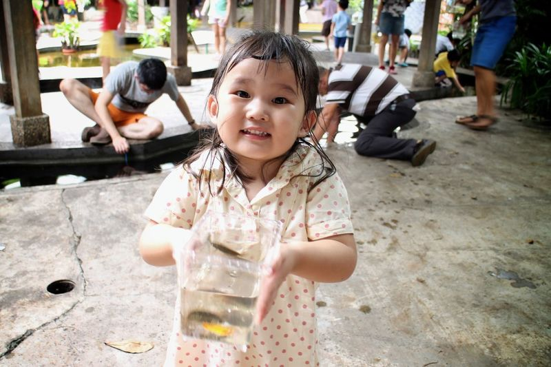 Portrait Of Smiling Girl Holding Water Container In Qian Hu Fish Farm Trading