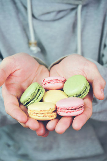 One Person Food Human Hand Food And Drink Holding Hand Freshness Midsection Human Body Part Healthy Eating Wellbeing Real People Fruit Focus On Foreground Front View Men Close-up Unrecognizable Person Lifestyles Finger Temptation Snack Macaroon Macarons Dessert