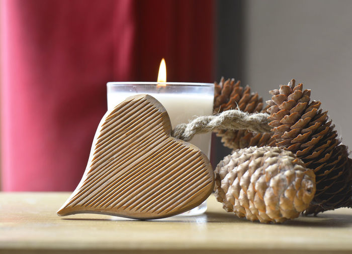 Love Romantic Burning Candle Close-up Fire Flame Heart Shape Indoors  Pine Cone Still Life Table Wooden