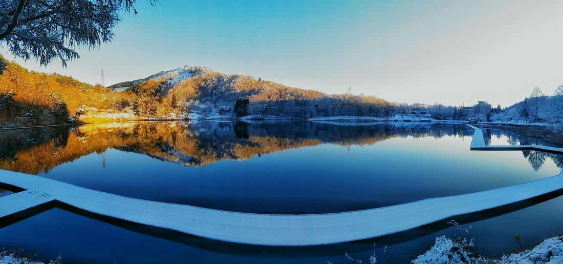 A Panoramic View Of A Beautiful Lake - I was on my way from Shibu Onsen to Matsumoto and I stumbled upon this lake. The early morning snow makes it looks even more beautiful! Sony Japan Japan Photography EyeEm EyeEm Best Shots EyeEmNewHere EyeEm Nature Lover EyeEm Gallery EyeEm Selects EyeEm Landscape Travel Destinations Calm Soft Tranquility Water Tree Mountain Lake Blue Reflection Winter Symmetry Sky Landscape Pine Woodland Snowcapped Mountain Reflection Lake Standing Water Snowcapped Snow Covered The Great Outdoors - 2018 EyeEm Awards The Traveler - 2018 EyeEm Awards