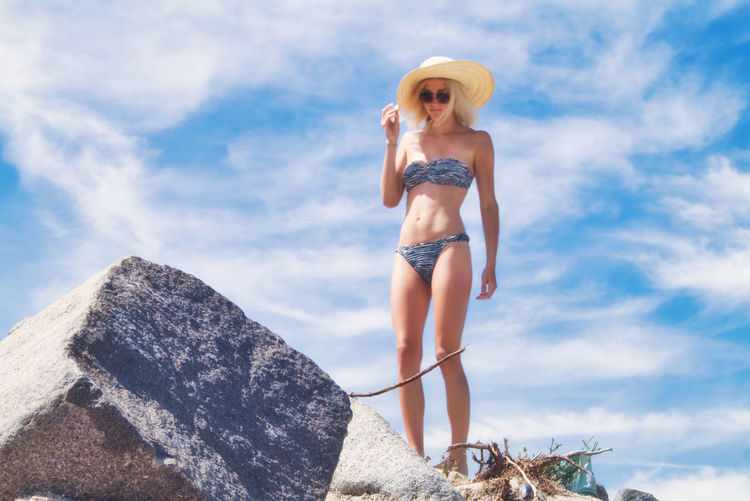Low angle view of woman in bikini with hat at empty beach against sky, scharbeutz