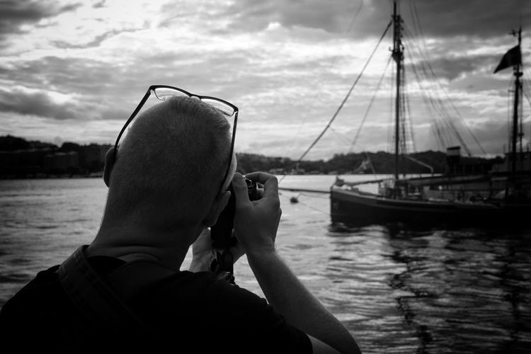Rear View Man Photographing Boat In Sea Against Cloudy Sky
