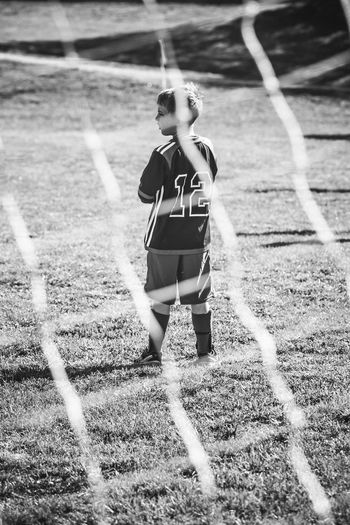 Rear view of boy standing on field