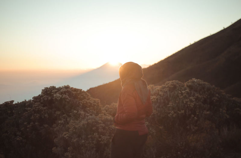 Rear view of woman looking at mountains during sunset