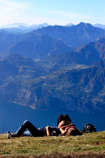 a couple is resting on the top of a mountain Alpen Beauty In Nature Blau Blue Couple Hill Idyllic Landscape Leisure Activity Lifestyles Love Mountain Mountain Range Nature Outdoors Relaxation Relaxing Resting Ruhe Sky Tourism Tourist Tranquil Scene Tranquility Vacations