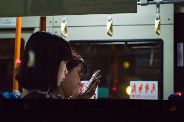 """Windows to another world. At night the glass on busses are windows to other worlds. Like movie screens, the frames show me the lives and stories of actors and passengers alike as the bus glides by. (Nikon D810 24-70mm f/2.8 ƒ/3.5 70mm 1/200"""" iso 6400) Copy Space Japan Mobile Phone Public Transportation Adult Bus Editorial  Friendship Headshot Illuminated Indoors  Night People Real People Streetphotography Telephone Togetherness Transportation Two People Urban Women Young Adult Young Women Mobility In Mega Cities Stories From The City The Traveler - 2018 EyeEm Awards It's About The Journey"""