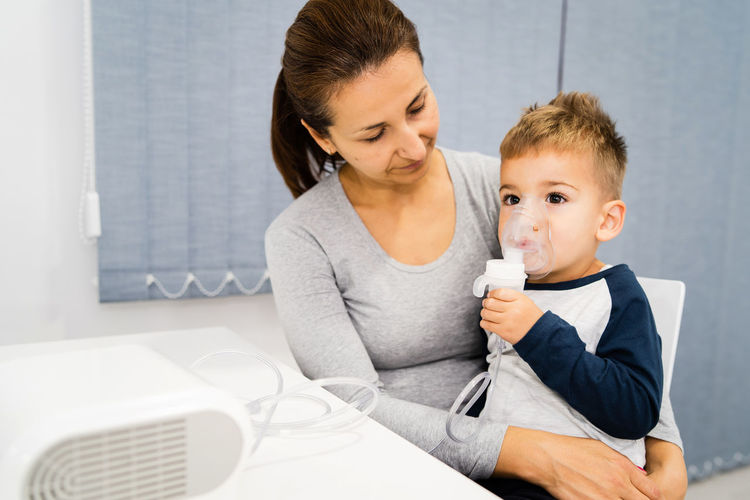 Mother and son with nebulizer on table