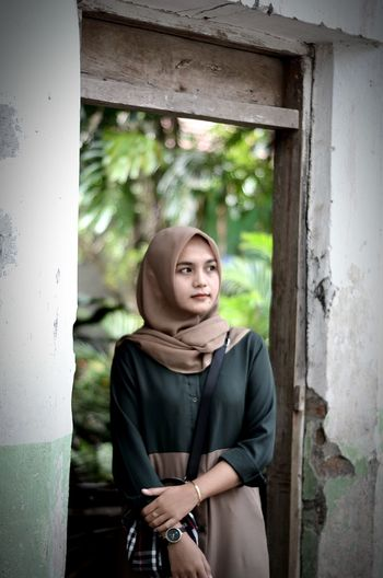 Young woman in hijab looking away while standing by abandoned building