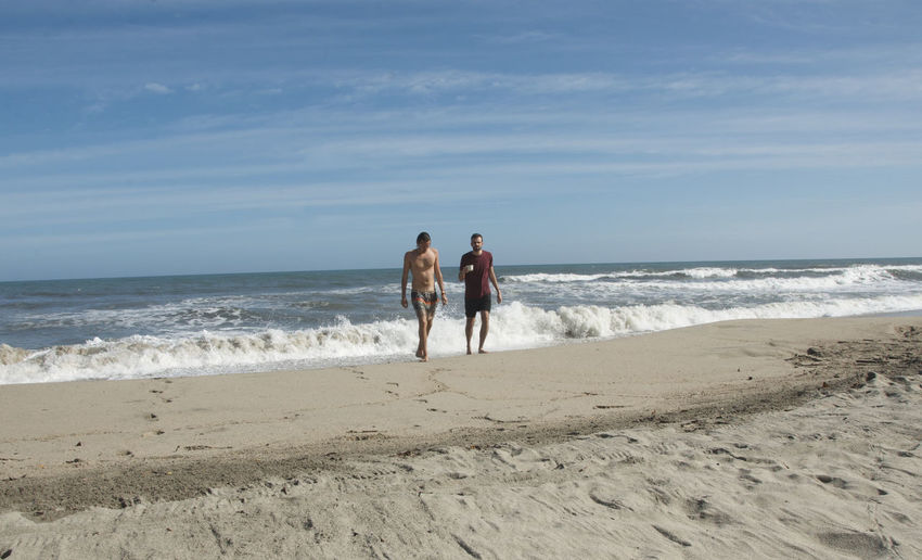 Male friends walking at beach against blue sky