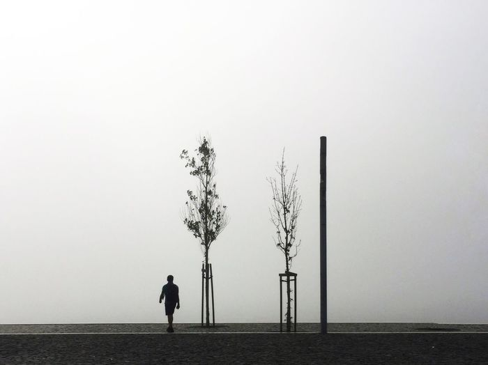 Silhouette Man Walking On Footpath Against Sky During Foggy Weather