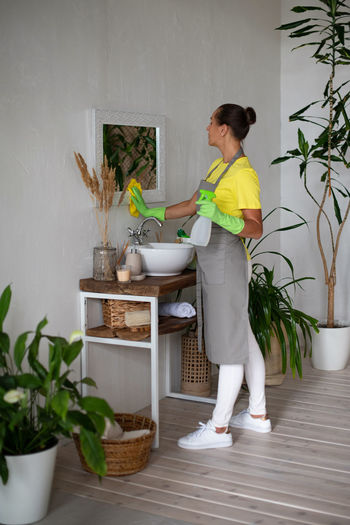 Woman standing by potted plant at home