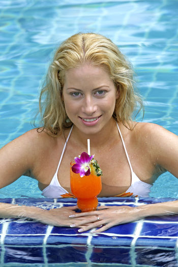 Portrait Of Smiling Young Woman With Cocktail In Swimming Pool