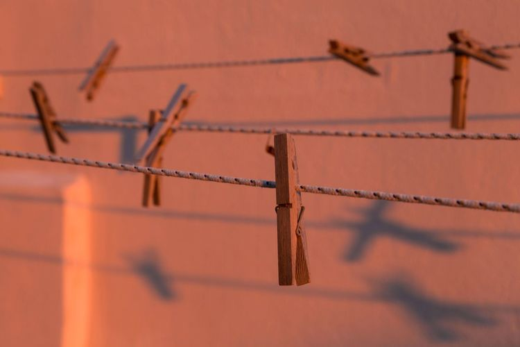Close-up of barbed wire fence against wall