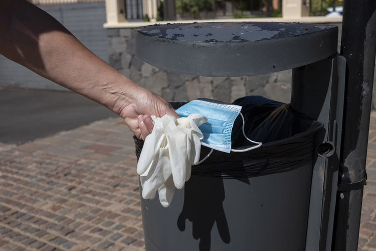 Cropped hand of person dumping glove and mask in garbage can
