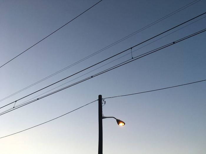 Low Angle View Of Street Light And Cables Against Sky At Dusk