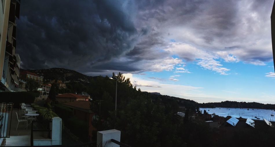 Panoramic view of village against cloudy sky