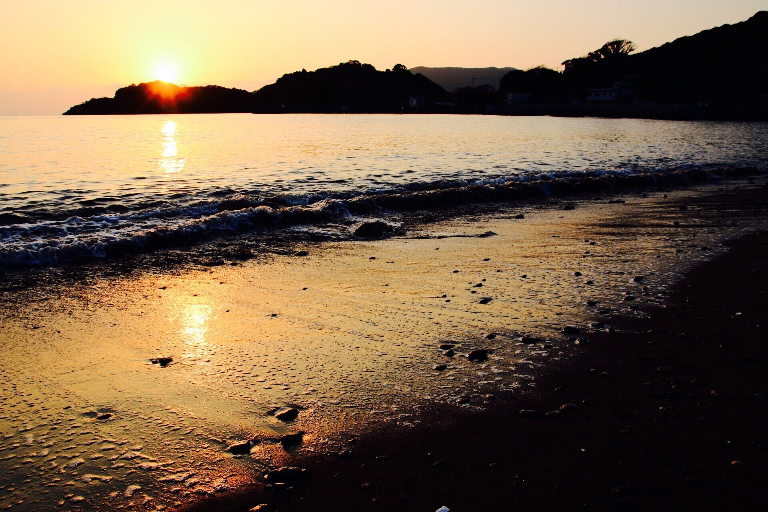 water, sunset, sun, sea, beach, tranquil scene, scenics, tranquility, reflection, shore, beauty in nature, sunlight, sky, nature, idyllic, silhouette, coastline, sunbeam, sand, mountain