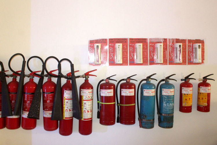 Indoors  Side By Side In A Row Container Large Group Of Objects No People Red Studio Shot Multi Colored Wall - Building Feature Choice Still Life Bottle Close-up Arrangement Variation Hanging Fire Extinguisher