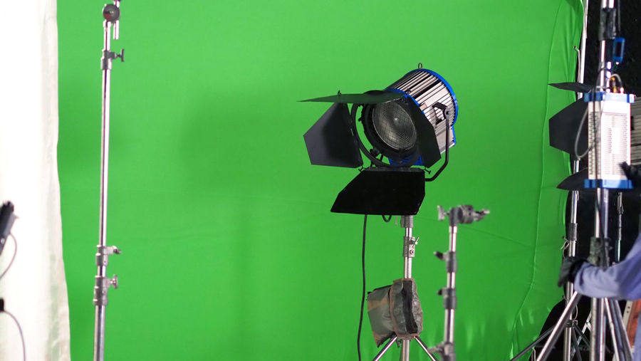 Big studio LED spotlight for video movie or photo film production with green screen background for chroma key technique in post lab process and professional equipment such as tripod and others. Arts Culture And Entertainment Behind The Scenes Camera - Photographic Equipment Electric Lamp Equipment Film Industry Film Studio Filming Green Color Indoors  Lighting Equipment No People Occupation Photo Shoot Photographic Equipment Photographing Photography Themes Studio Studio; Light; Video; Stage; Lights; Spotlight; Equipment; Film; Background; White; Photography; Photo; Fresnel; Isolated; Spot; Lamp; Movie; Production; Stand; Black; Bright; Camera; Illuminated; Lighting; Backdrop; Art; Scene; Media; Design; Technical;  Technology Television Industry Television Studio Tripod
