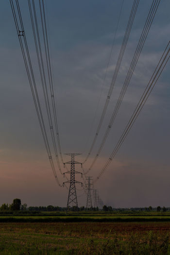 Electricity pylon on field against sky during sunset