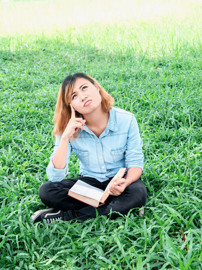 Thoughtful Woman Reading Book While Sitting On Field