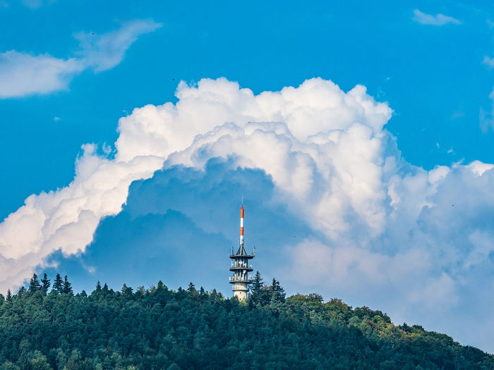 Low angle view of tv- tower against cloudy sky