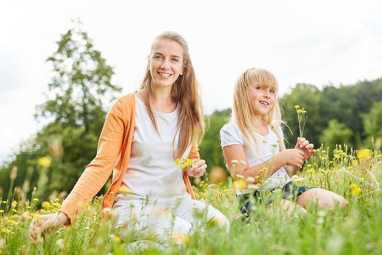 Smiling Mother And Daughter Sitting On Field Amidst Plants