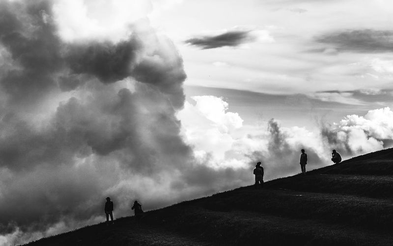 Silhouette people on standing on hill against cloudy sky