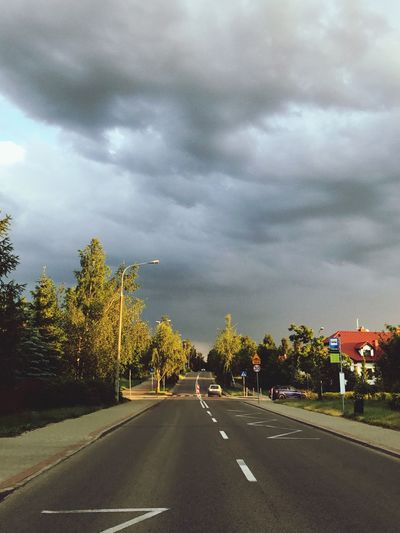 Road by trees against cloudy sky
