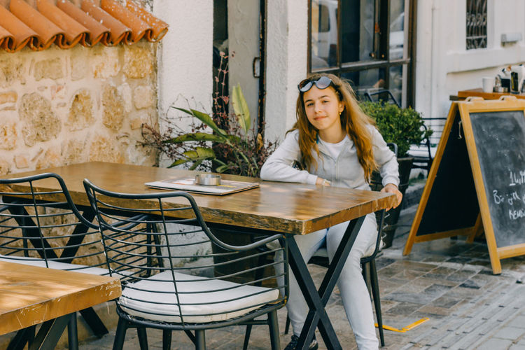 Portrait of girl sitting at table outdoor cafe