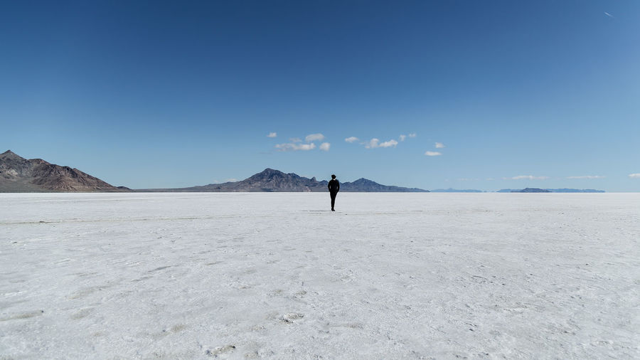 Rear View Of Person Standing On Salt Flat Against Sky