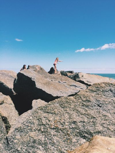 Low angle view of girls on rock formations against sea