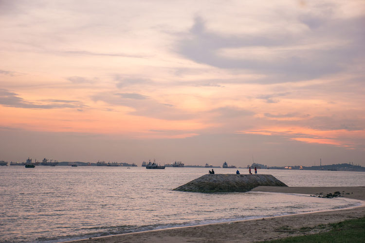Sunset by the beach. Taken in Singapore at East Cpast Parkway during the golden hour. Sunset Beach Sea Sand Sky Cloud - Sky Sunny Water Outdoors Horizon Over Water Low Tide Landscape Fishing Silhouette Sitting At The Bench Blue Nautical Vessel Nature Vacations Sun Full Length