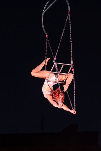Low angle view of woman hanging on rope against black background