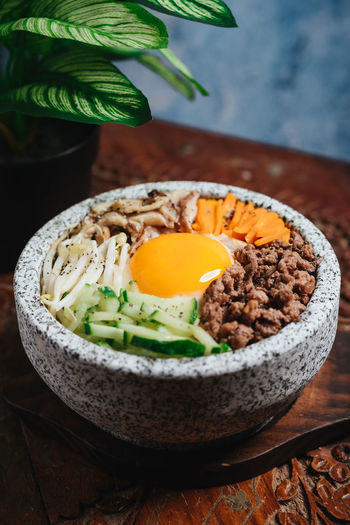 Bibimbap Korean Food Bowl Close-up Egg Focus On Foreground Food Food And Drink Freshness Garnish Healthy Eating High Angle View Indoors  Japanese Food Leaf Plant Ready-to-eat Serving Size Still Life Table Vegetable Wellbeing Wood - Material