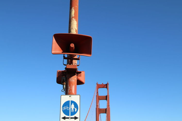 Low angle view of megaphone speakers against golden gate bridge