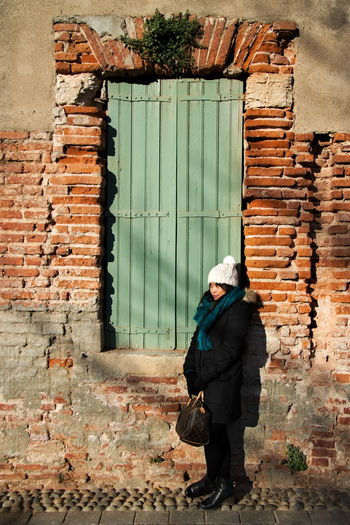 Full length of woman in warm clothing standing by old building