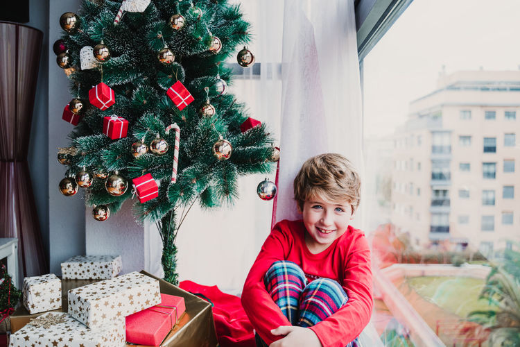 Portrait of boy sitting by christmas tree at home