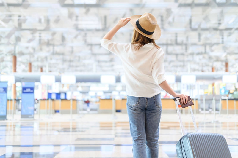 Rear view of woman wearing hat with suitcase walking at airport