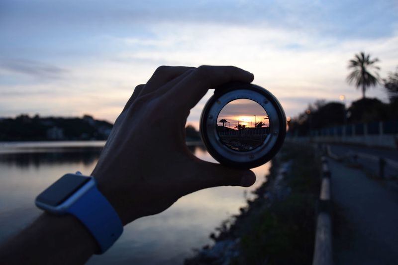 Close-up of hand holding magnifying glass against sea during sunset