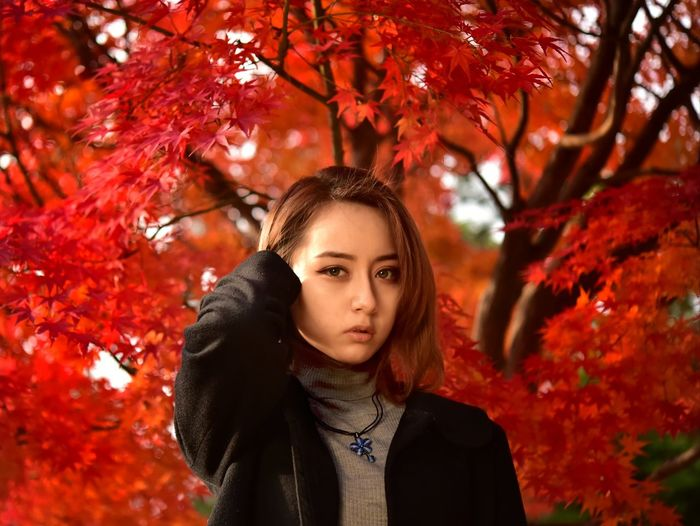 Portrait of beautiful young woman standing by autumn leaves
