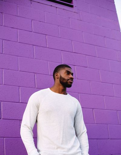Portrait Of Man Standing Against Purple Wall