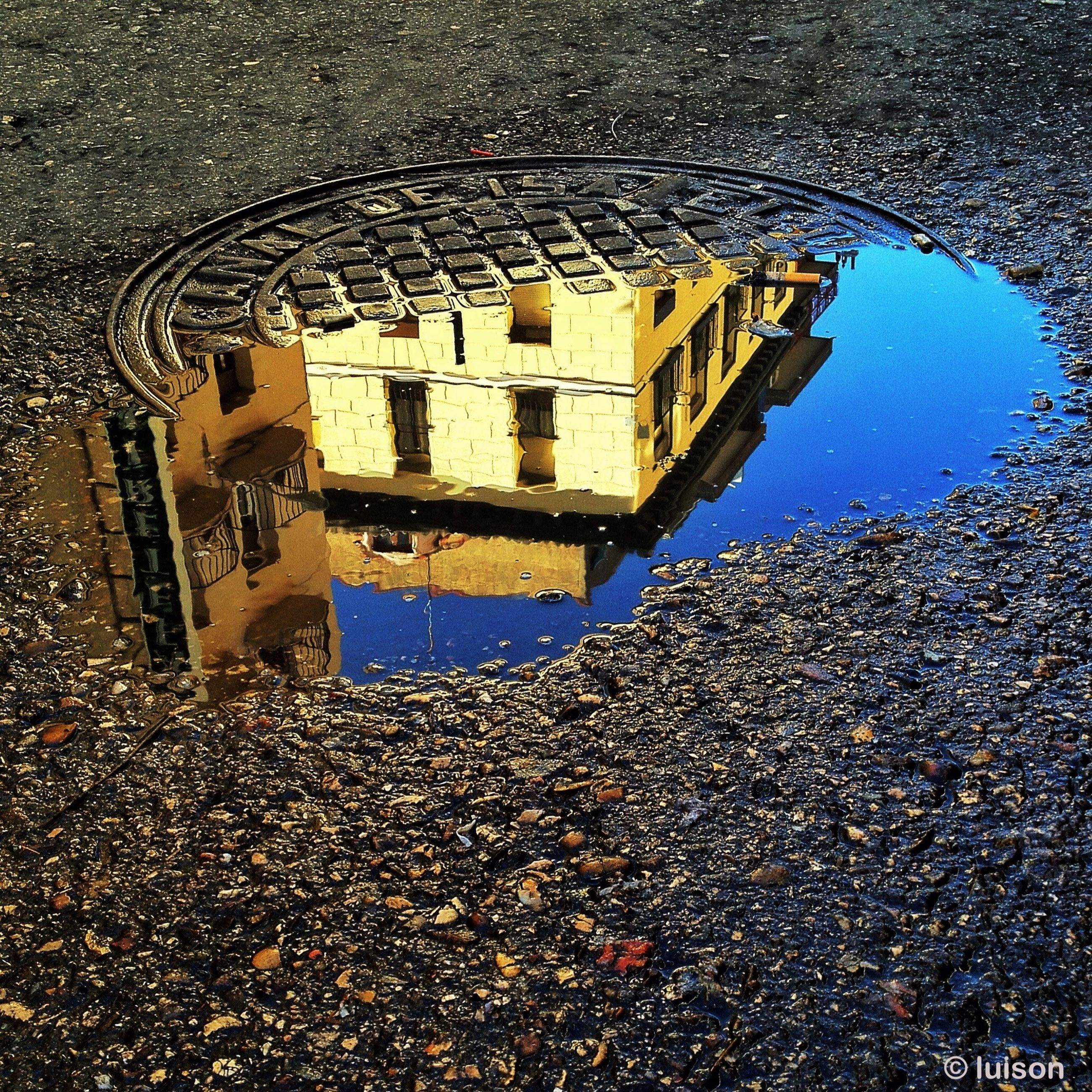 architecture, building exterior, built structure, puddle, street, water, high angle view, wet, city, reflection, road, sky, asphalt, building, outdoors, day, rain, transportation, window, no people