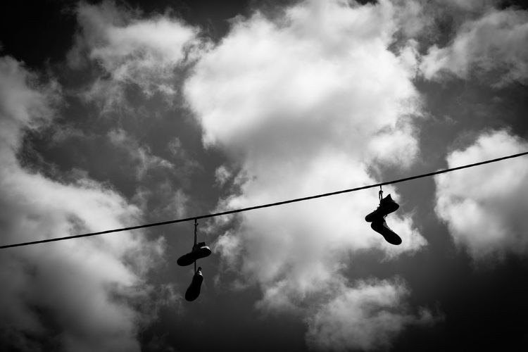 Low angle view of shoes hanging on wire against cloudy sky