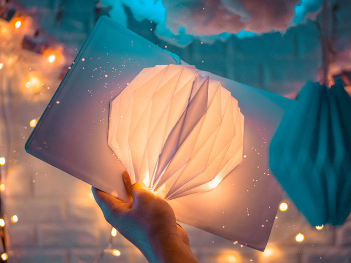 Cropped hand holding illuminated decoration
