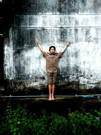 Full length of boy wearing police uniform while standing with arms raised against weathered wall