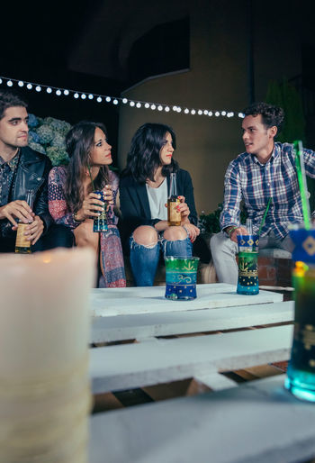 Young friends talking and drinking in a outdoors party. Friendship and celebrations concept. Beer Celebration Cocktail Friends Fun Happiness Happy Millenials Sitting Young Alcohol Bottle Cheerful Drink Entertainment Four People Friendship Group Night Nightlife Outdoors Party People Sofa Vertical