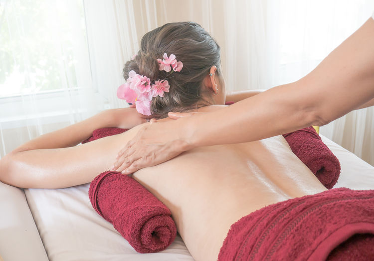 Cropped hands of person massaging woman